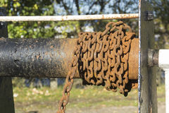 Rusty chain on canal lock gear. Rusty chain on a spindle, a section of a little used or disused part of winch winding gear on a canal lock in the UK Stock Photos
