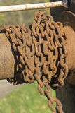 Rusty chain on canal lock gear. Rusty chain on a spindle, a section of a little used or disused part of winding gear on a canal lock in the UK Stock Image