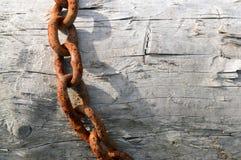 Rusty Chain en la madera de deriva Imagen de archivo libre de regalías