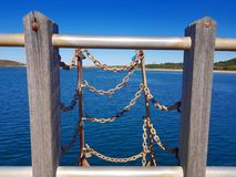 Chains and ocean from a jetty royalty free stock photo