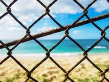 Rusty Chain Link Fence delante de la playa Fotos de archivo