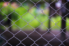Rusty Chain Link Fence of steel netting on blur background. Wired metal fence in vintage tone Stock Photo