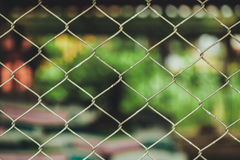 Rusty Chain Link Fence of steel netting on blur background. Wired metal fence in vintage tone Stock Photography