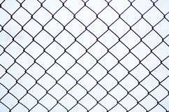 Rusty chain link fence of steel netting. On white snow background in cold winter day Royalty Free Stock Image
