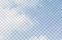 Rusty chain link fence under the sky background. Royalty Free Stock Image
