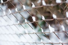 Rusty chain link iron fence in winter. Rusty chain link iron fence covered in fresh snow in wintertime Stock Photography