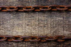 Rusty chain on the old wooden background. Rusty chain on the top and bottom on the old wooden background Stock Images