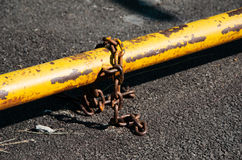 Rusty chain with old yellow security bar Stock Photos