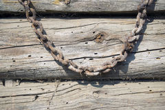 Rusty chain over wood Stock Photos