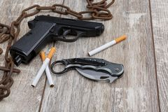 The rusty chain, a pistol, ammunition and several cigarettes. On the wooden floor there is an old rusty chain, a black pistol, several scattered ammunition and Stock Photo
