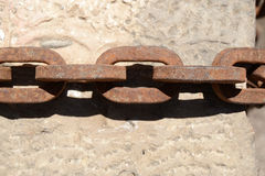 Rusty chain. Rests on a stone Royalty Free Stock Image