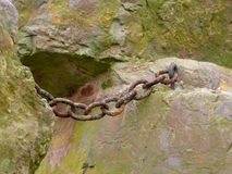 Rusty chain on a rock Royalty Free Stock Photos
