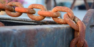 Rusty chain. A rusty shackle chain hanging over a girder Royalty Free Stock Photo