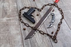 Rusty chain in the shape of heart and machete on a wooden background. Top view from an angle. A rusty chain in the shape of a heart and a machete that pierces royalty free stock image