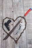 Rusty chain in the shape of heart and machete on a wooden background. View from above. A rusty chain in the shape of a heart and a machete that pierces the heart stock photography