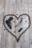 Rusty chain in the shape of a heart in which a gun on a wooden background. View from above. A rusty chain in the shape of a heart in which a gun, bullets, a stock photography