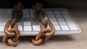 Rusty chains on computer keyboard in close-up on dark background Royalty Free Stock Photography