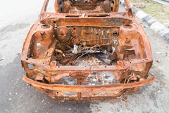 Rusty chassis of a burnt car abandoned by the side of the street Royalty Free Stock Images