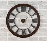 Rusty clock hanging on white brick wall Royalty Free Stock Photo