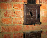 Rusty closed metal door in red brick sooty furnace.  stock images
