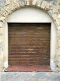 Rusty closed rolling portcullis of shop. Rusty shop rolling portcullis of stone house is closed Stock Photo