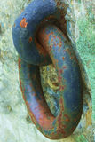 Rusty colorful harbor chain attached to cement block. Very colorful, with the rust taking over the blue paint of the large chain that is attached to weather Royalty Free Stock Photo