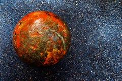 Rusty concrete ball on wet dark asphalt. stock images
