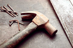 Construction tools. Old hammer, hand saw and nails Stock Images