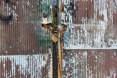 Rusty corrugated steel sheet gate locked with a padlock Stock Photos
