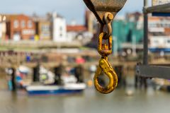 A rusty crane hook with blurry background. Of Bridlington harbour, East Riding of Yorkshire, UK Stock Photos