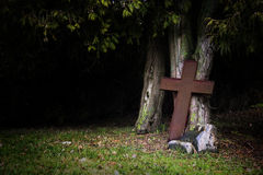 Rusty cross made of metal leaning against old tree trunks in sha Royalty Free Stock Image