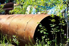 A rusty culvert laying in a scape metal yard.  Stock Image