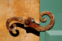 Rusty Curves. Close-up of an old rusty architectural element used to hold open wooden shutters Stock Images