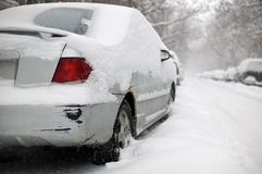 Rusty damaged car stuck in the. A damaged car covered in snow during a storm royalty free stock photography
