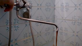 A rusty dirty water pours from the tap. A dirty brown running water is unfit for drinking.