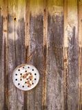 Rusty disc with holes. Rusty metal disc with holes on a wooden wall. Vertical picture Royalty Free Stock Photography