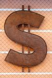 Rusty dollar sign on the wall of a closed mesh. Vertically framed shot stock photography