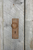 Rusty dooknob. Old rusted doorknob with keyhole in weathered wooden door stock image