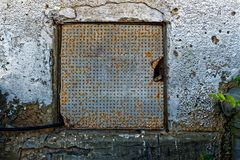 Rusty door with circular holes. In it and a pipe coming out. attached to a white wall Royalty Free Stock Images