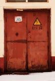 Rusty door, danger high voltage. Grunge rusty orange door, danger high voltage keep out in russian Stock Images