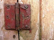 Rusty door hinge on scratched up wooden door. Rusty red hinge, it's red paint peeling, on a light brown, weathered and scratched up garden door Stock Image