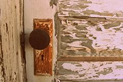 Rusty Door Knob with White Chippy Paint. Rusty door knob on the front of a old wooden door with white chippy paint Stock Photography