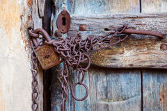 Rusty door lock and chain on an old door Royalty Free Stock Image