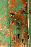 Rusty doorknob and latch on old weathered green door . stock photography