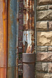 Rusty Drain Pipe. A view of a rusty gutter downspout pouring into an old rusted pipe that's attached to a stone and brick building Royalty Free Stock Images
