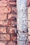Rusty drain pipe with coiled wire on red brick wall. Grunge texture stock photography