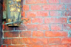 Rusty drain pipe with coiled wire on red brick wall, grunge texture. Background royalty free stock image