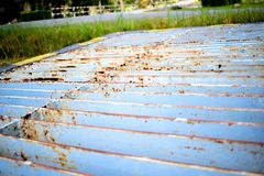 Rusty drained ditch cover. At side of the street Royalty Free Stock Photo