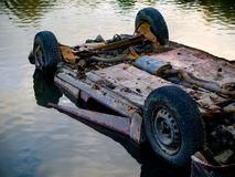Rusty Dumped Car in Water Pond. Lake Polluting Royalty Free Stock Images