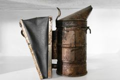 Rusty, dusty and very old bee smoker placed on white shelf.  Royalty Free Stock Images